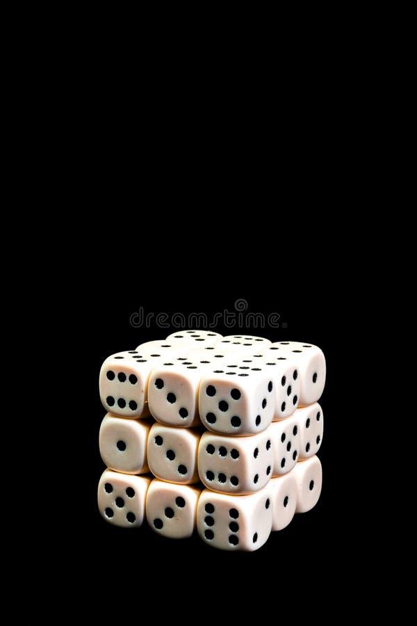 Dobbel in de vorm van een kubus op een zwarte achtergrond, isoleer royalty-vrije stock afbeeldingen