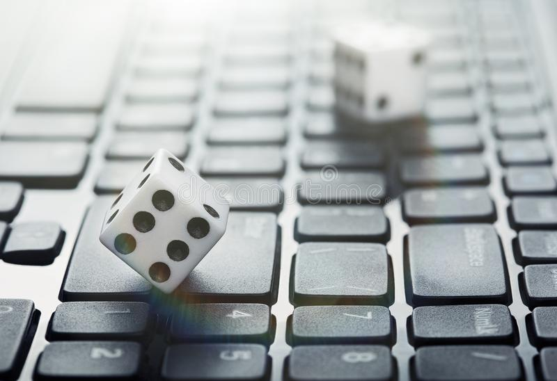 Dobbel op laptop computertoetsenbord Ð ¡ oncept van online gokkend en online casino Creatief idee met duivels` s beenderen en PC- stock foto's