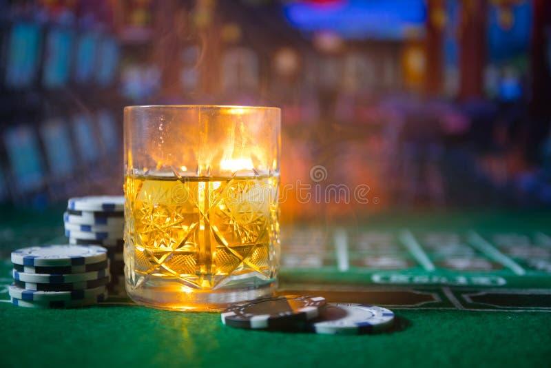Dobbleri-, f?rm?genhet-, lek- och underh?llningbegrepp - som ?r n?ra upp av kasinochiper och whiskyexponeringsglas p? tabellen fotografering för bildbyråer