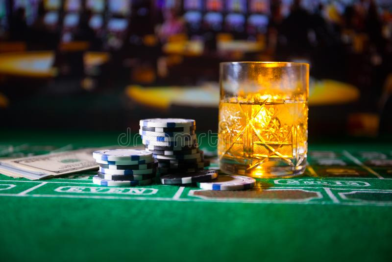 Dobbleri-, f?rm?genhet-, lek- och underh?llningbegrepp - som ?r n?ra upp av kasinochiper och whiskyexponeringsglas p? tabellen royaltyfri bild