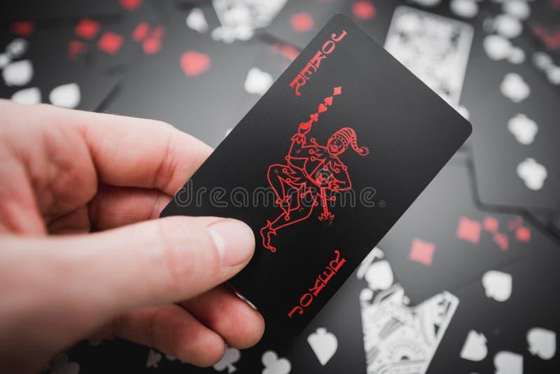 dobbleri Jokerkortet i hand ovanför svart färgade spela kortbakgrund royaltyfria bilder