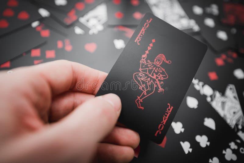 dobbleri Jokerkortet i hand ovanför svart färgade spela kortbakgrund arkivbild
