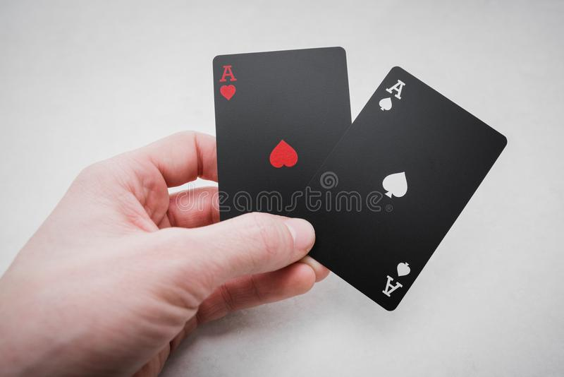 dobbleri Två överdängare i hand i svart färgade spela kort royaltyfri foto
