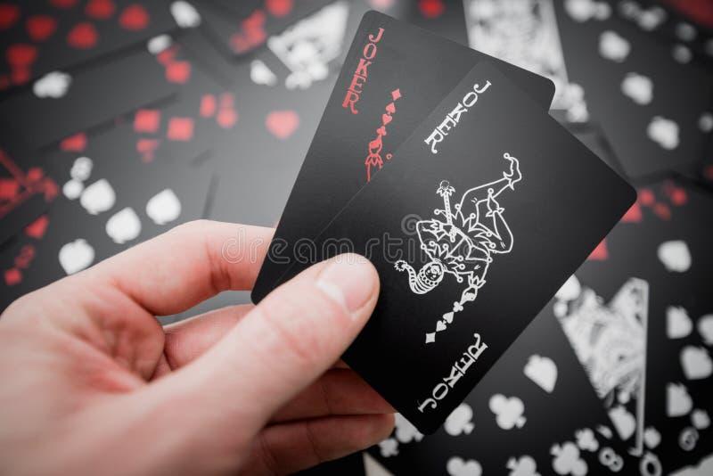 dobbleri Två jokerkort i hand ovanför svart färgade spela kortbakgrund royaltyfri bild