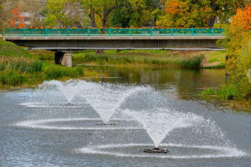 Dobele, Letonia Paisaje de la ciudad del otoño con el río, el puente y las fuentes fotografía de archivo libre de regalías
