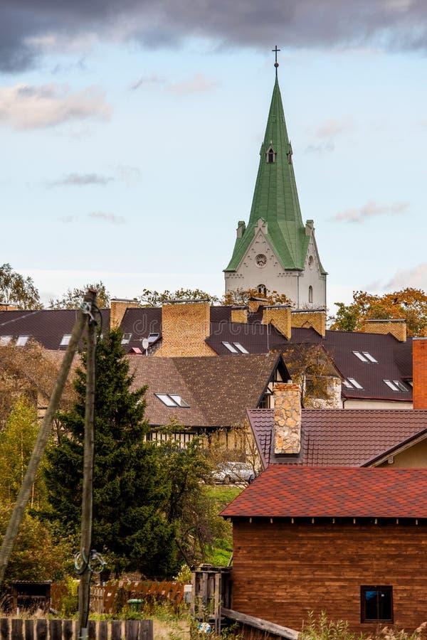Dobele, Lettonia Vista della torre di chiesa e dei tetti privati della casa fotografia stock libera da diritti
