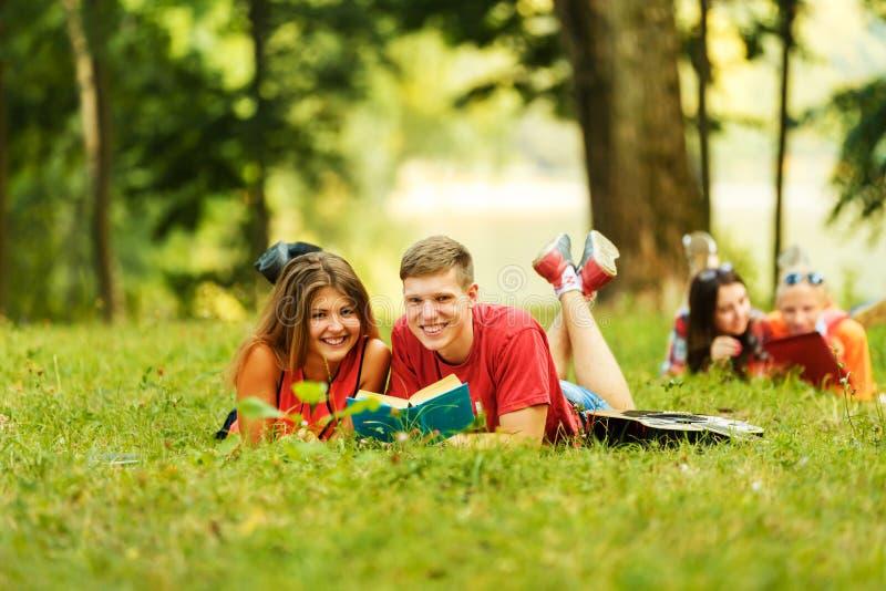 Dobierać do pary pomyślnych uczni z podręcznikiem w parku obraz stock