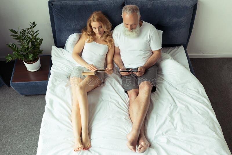Dobiera się czytelniczą książkę i używać cyfrową pastylkę podczas gdy kłamający na łóżku w domu zdjęcie stock