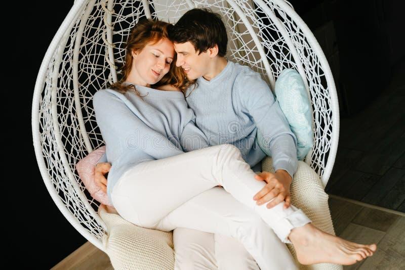 Dobiera się dziewczyny i faceta przytulenie na dużym krześle zdjęcie stock