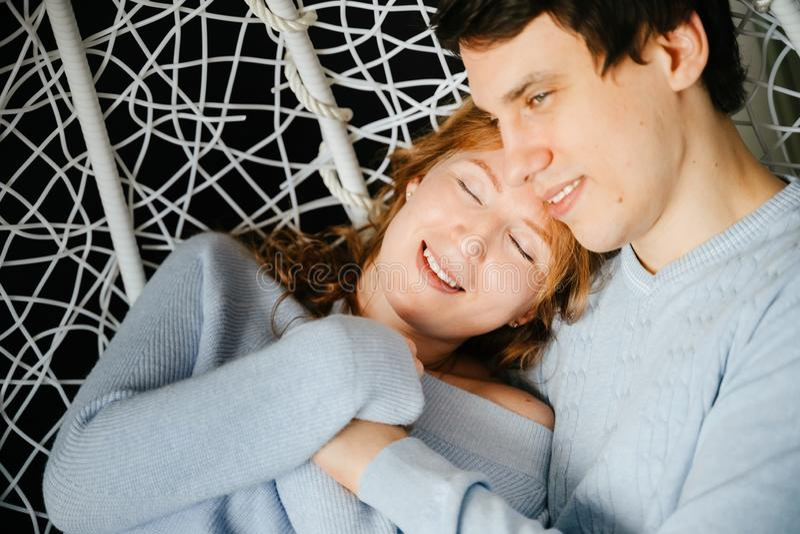 Dobiera się dziewczyny i faceta przytulenie na dużym krześle zdjęcia stock