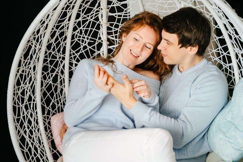Dobiera się dziewczyny i faceta przytulenie na dużym krześle obraz stock