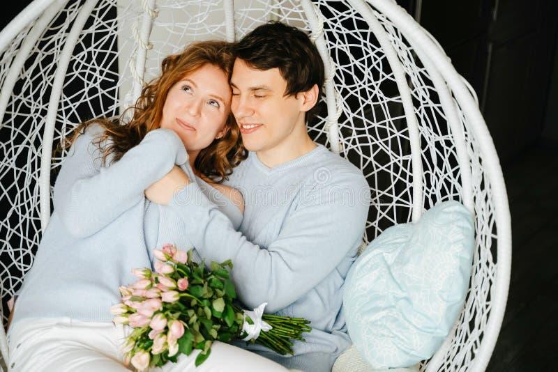 Dobiera się dziewczyny i faceta przytulenie na dużym krześle z bukietem róże obrazy stock