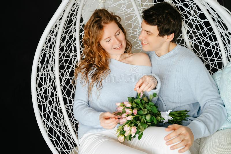 Dobiera się dziewczyny i faceta przytulenie na dużym krześle z bukietem róże zdjęcia stock