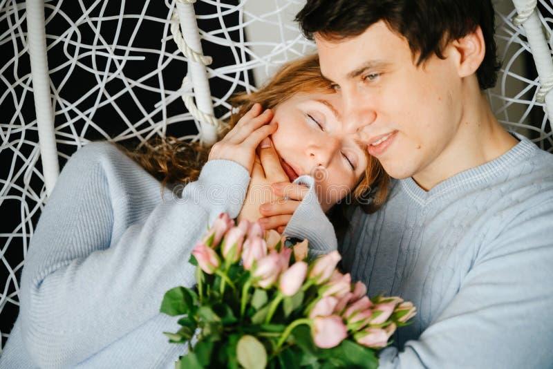 Dobiera się dziewczyny i faceta przytulenie na dużym krześle z bukietem róże fotografia royalty free