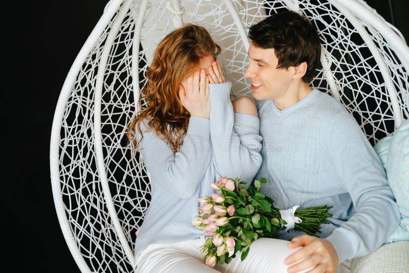 Dobiera się dziewczyny i faceta przytulenie na dużym krześle z bukietem róże obrazy royalty free