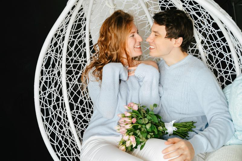 Dobiera się dziewczyny i faceta przytulenie na dużym krześle z bukietem róże zdjęcia royalty free