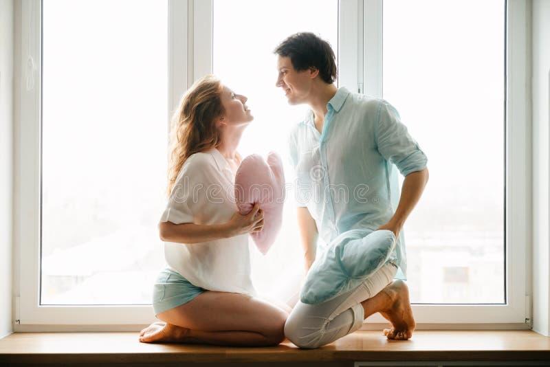 Dobiera się dziewczyny i faceta sztukę z poduszkami blisko okno fotografia royalty free