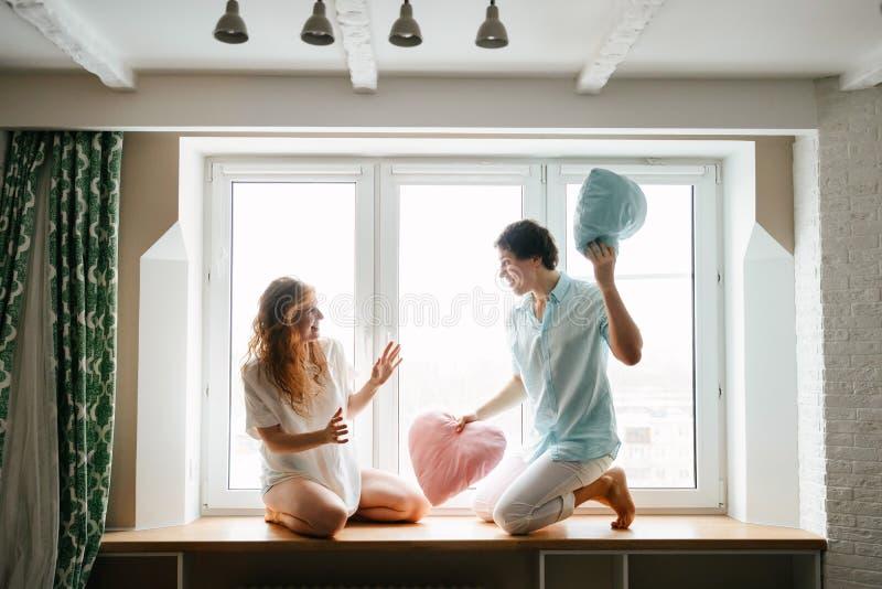 Dobiera się dziewczyny i faceta sztukę z poduszkami blisko okno obraz stock