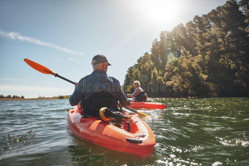 Dobiera się kayaking w jeziorze na słonecznym dniu zdjęcie royalty free