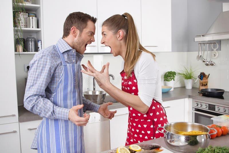 Dobiera się krzyczeć przy each inny przy kuchnią - stres. zdjęcie stock