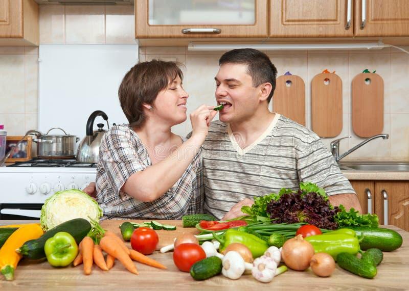 Dobiera się kucharstwo w kuchennym wnętrzu z świeżymi owoc i warzywo, zdrowym karmowym pojęciem, kobietą i mężczyzna, obrazy stock