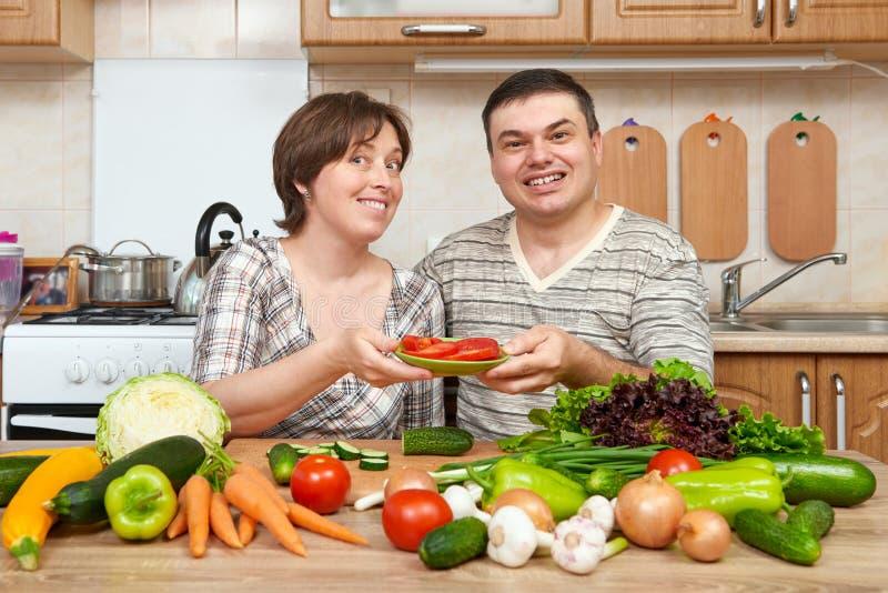 Dobiera się kucharstwo w kuchennym wnętrzu z świeżymi owoc i warzywo, zdrowym karmowym pojęciem, kobietą i mężczyzna, zdjęcia royalty free