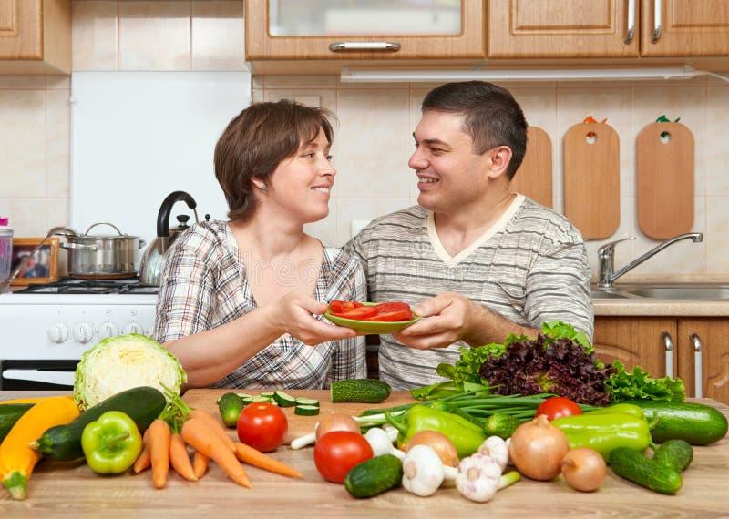 Dobiera się kucharstwo w kuchennym wnętrzu z świeżymi owoc i warzywo, zdrowym karmowym pojęciem, kobietą i mężczyzna, zdjęcie royalty free