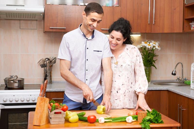 Dobiera się kucharstwo w kuchennym wnętrzu z świeżymi owoc i warzywo, zdrowym karmowym pojęciem, kobieta w ciąży i mężczyzna, obrazy stock