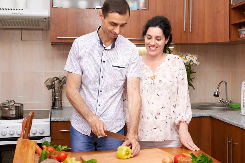 Dobiera się kucharstwo w kuchennym wnętrzu z świeżymi owoc i warzywo, zdrowym karmowym pojęciem, kobieta w ciąży i mężczyzna, zdjęcie stock
