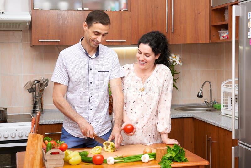 Dobiera się kucharstwo w kuchennym wnętrzu z świeżymi owoc i warzywo, zdrowym karmowym pojęciem, kobieta w ciąży i mężczyzna, zdjęcia royalty free