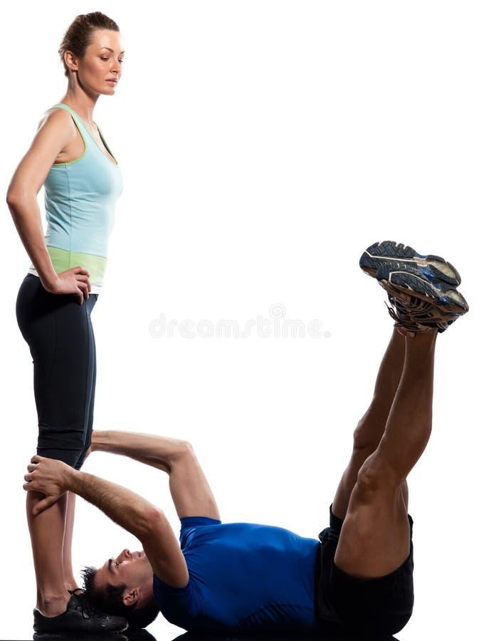 Dobiera się, mężczyzna i kobieta robi abdominals podnosi trening pcha obrazy stock