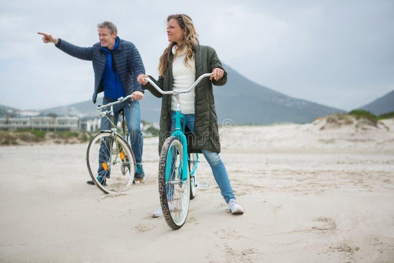 Dobiera się na bicyklu wskazuje przy odległością na plaży obrazy royalty free