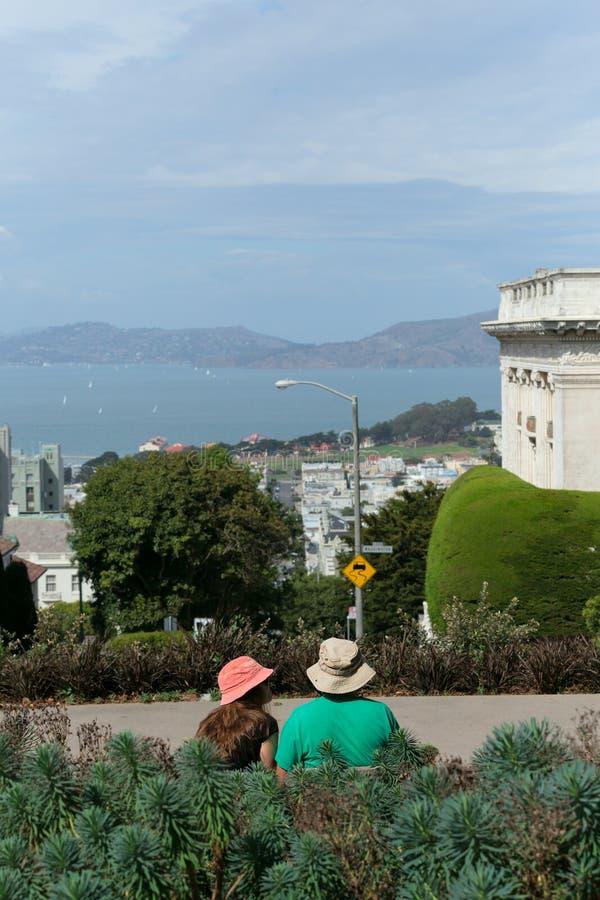 Dobiera się obsiadanie na ławce i patrzeć na San Fransisco citysca zdjęcie stock
