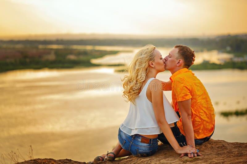 Dobiera się obsiadanie na banku rzeka przy zmierzchem buziak obrazy royalty free