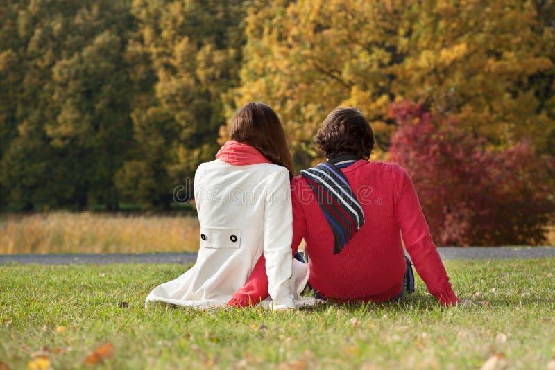Dobiera się obsiadanie na ziemi w parku zdjęcie royalty free