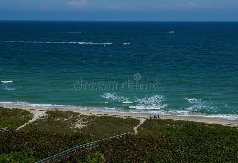 Dobiera się obsiadanie przy plażą patrzeje ocean obrazy royalty free