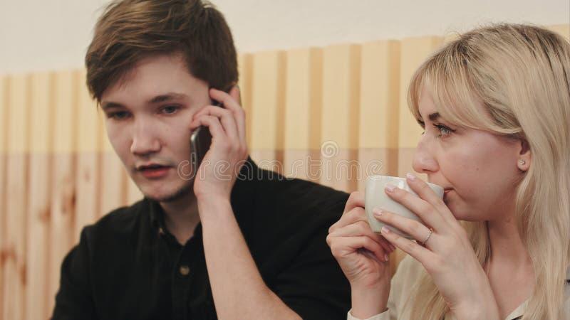 Dobiera się obsiadanie w bufecie, mężczyzna dzwoni telefonem komórkowym, kobieta pije kawę obraz stock