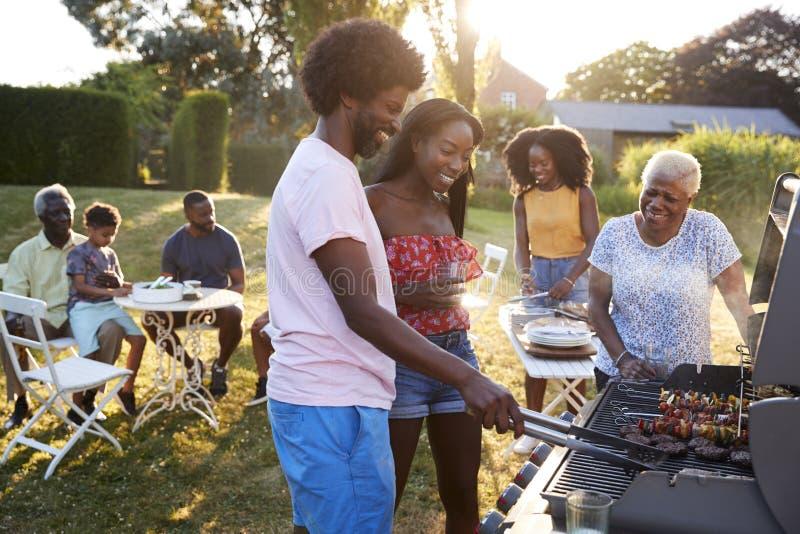 Dobiera się opieczenie przy czarnym wielo- pokolenie rodziny grillem obraz stock