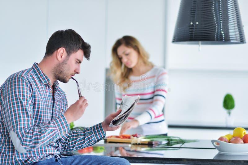 Dobiera się pozycję i obsiadanie przy kuchnią podczas gdy ono uśmiecha się, mężczyzna i czyta gazetę i trzyma kubek przed pracą obraz royalty free