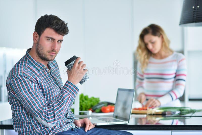 Dobiera się pozycję i obsiadanie przy kuchnią podczas gdy ono uśmiecha się, mężczyzna i czyta gazetę i trzyma kubek przed pracą obraz stock