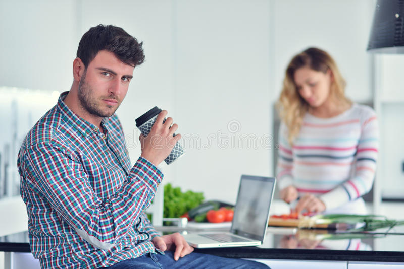 Dobiera się pozycję i obsiadanie przy kuchnią podczas gdy ono uśmiecha się, mężczyzna i czyta gazetę i trzyma kubek przed pracą fotografia stock