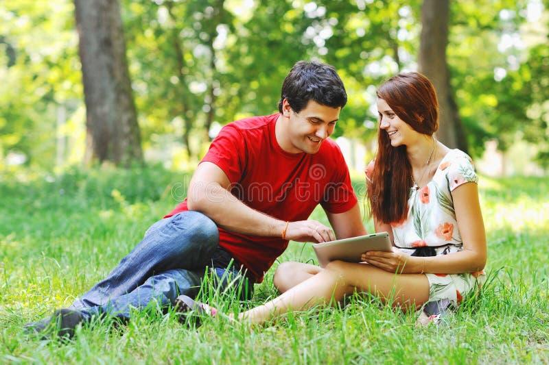 Dobiera się relaksować wpólnie w lato parku z pastylka komputeru komputerem osobistym zdjęcie royalty free