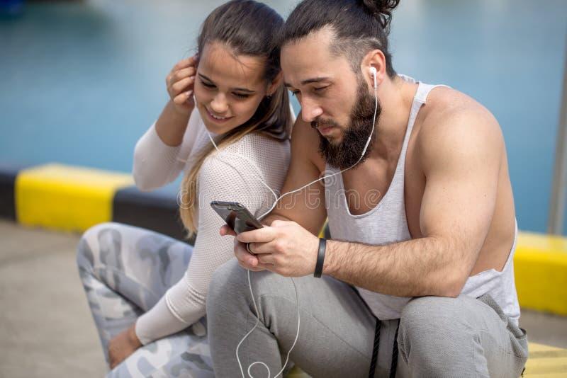 Dobiera się słuchanie muzyka wpólnie używa jeden słuchawki siedzi na molu zdjęcie royalty free