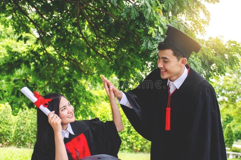 Dobiera się szczęśliwych ono uśmiecha się absolwentów i gratuluje each inny, kobieta uczni przyjaciele trzyma dyplomy w skalowani zdjęcie royalty free