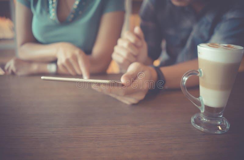 Dobiera się używać cyfrowego pastylka komputer wpólnie w sklepie z kawą, nowożytny biznesowy edukacji styl życia pojęcie obraz stock