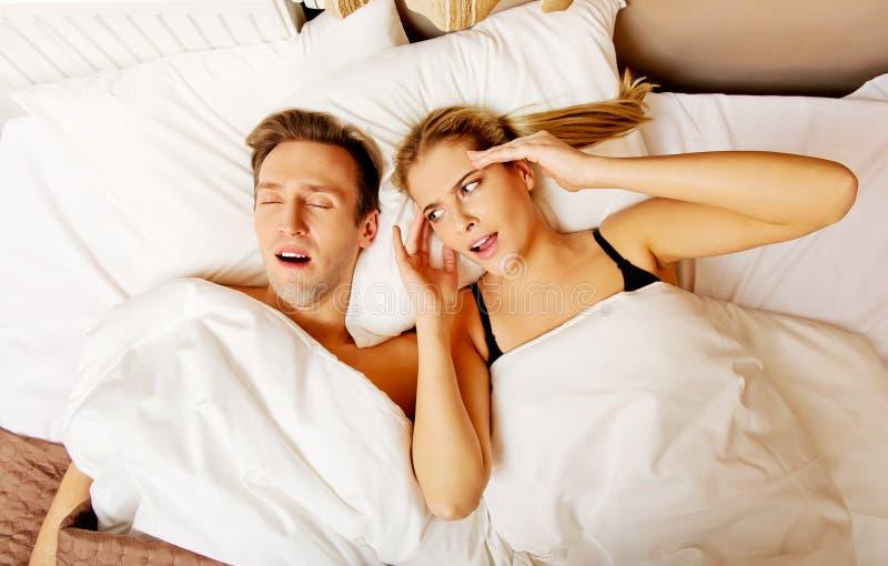 Dobiera się w łóżku, mężczyzna chrapa kobieta no może spać obraz stock
