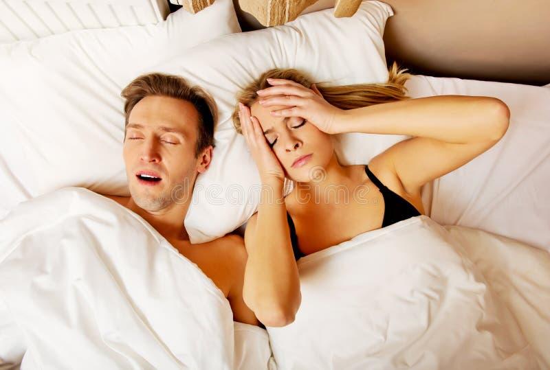 Dobiera się w łóżku, mężczyzna chrapa kobieta no może spać obrazy royalty free