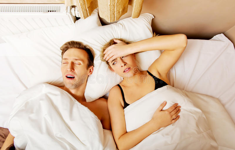 Dobiera się w łóżku, mężczyzna chrapa kobieta no może spać zdjęcia royalty free