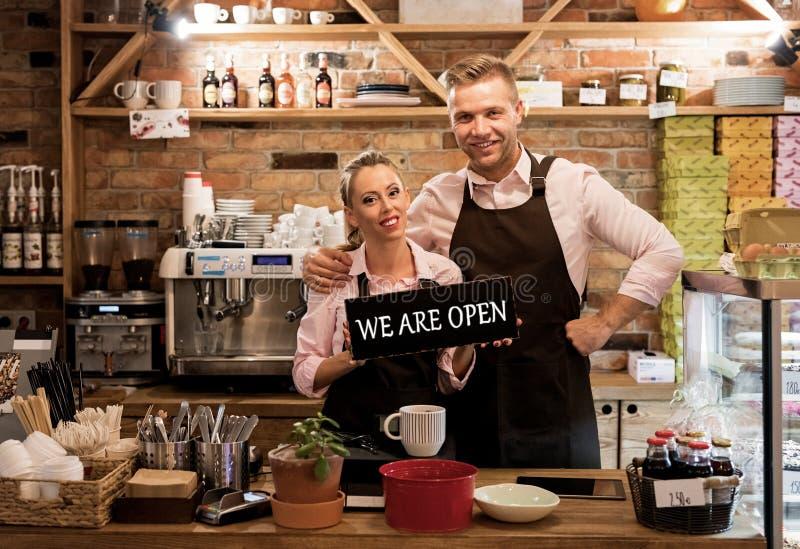 Dobiera się w ich nowej kawiarni, dumni wiadomości właściciel biznesu obraz royalty free