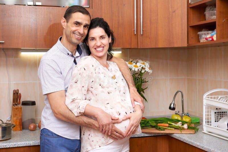 Dobiera się w kuchennym wnętrzu z świeżymi owoc i warzywo, zdrowym karmowym pojęciem, kobieta w ciąży i mężczyzna, obrazy stock